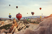Hot air balloon flying over rock landscape at Cappadocia Turkey. Cappadocia with its valley, ravine, hills, located between the volcanic mountains in Goreme National Park.