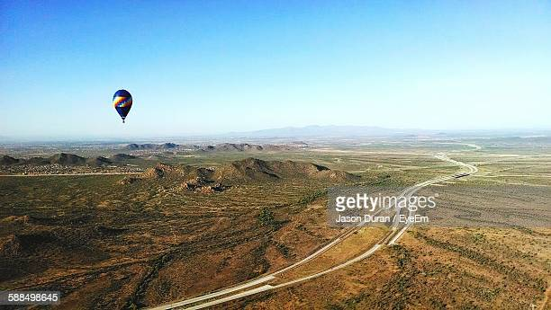 Hot Air Balloon Flying Over Scenic Landscape Against Sky