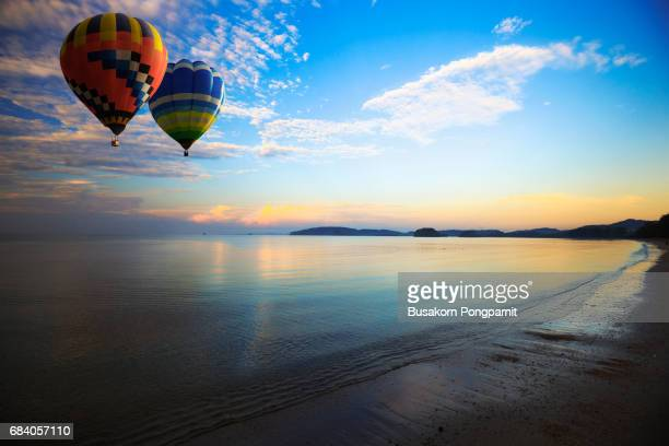 Hot air balloon flying over the sea, tropical sunset on the beach beautiful sunset