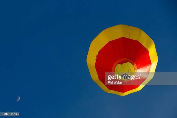 A hot air balloon flys under the moon over the Hamilton Lake during the Mass Ascension on the opening day of Balloons Over Waikato on March 22 2017...