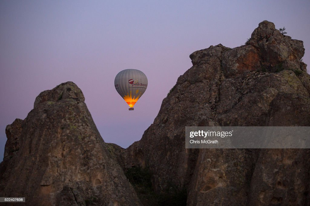 A hot air balloon is seen over rock formations on April 18, 2016 in Nevsehir, Turkey. Cappadocia, a historical region in Central Anatolia dating back to 3000 B.C is one of the most famous tourist sites in Turkey. Listed as a World Heritage Site in 1985, and known for its unique volcanic landscape, fairy chimneys, large network of underground dwellings and some of the best hot air ballooning in the world, Cappadocia is preparing for peak tourist season to begin in the first week of May. Despite Turkey's tourism downturn, due to the recent terrorist attacks, internal instability and tension with Russia, local vendors expect tourist numbers to be stable mainly due to the unique activities on offer and unlike other tourist areas in Turkey such as Antalya, which is popular with Russian tourists, Cappadocia caters to the huge Asian tourist market.