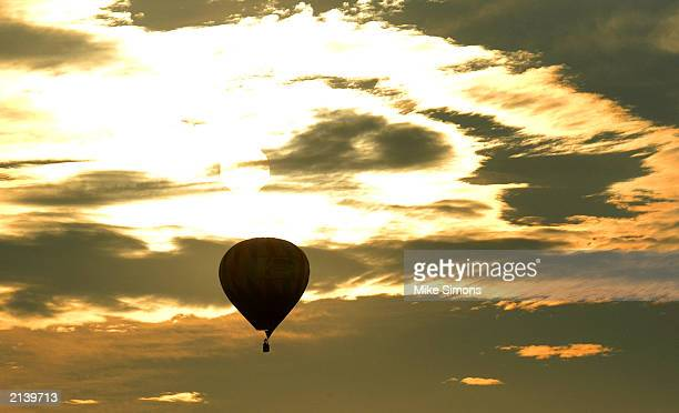 A hot air balloon is silhouetted against the sunrise as it takes part in a mass ascension during the Inventing Flight celebration at the United...