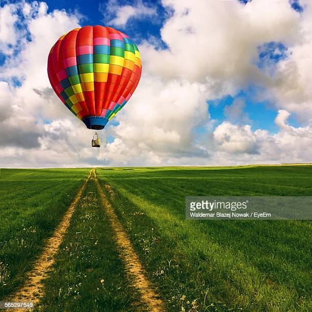 Hot Air Balloon Over Grassy Field Against Cloudy Sky