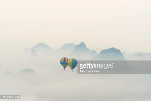 Hot air balloon ride at dawn over Karst mountains
