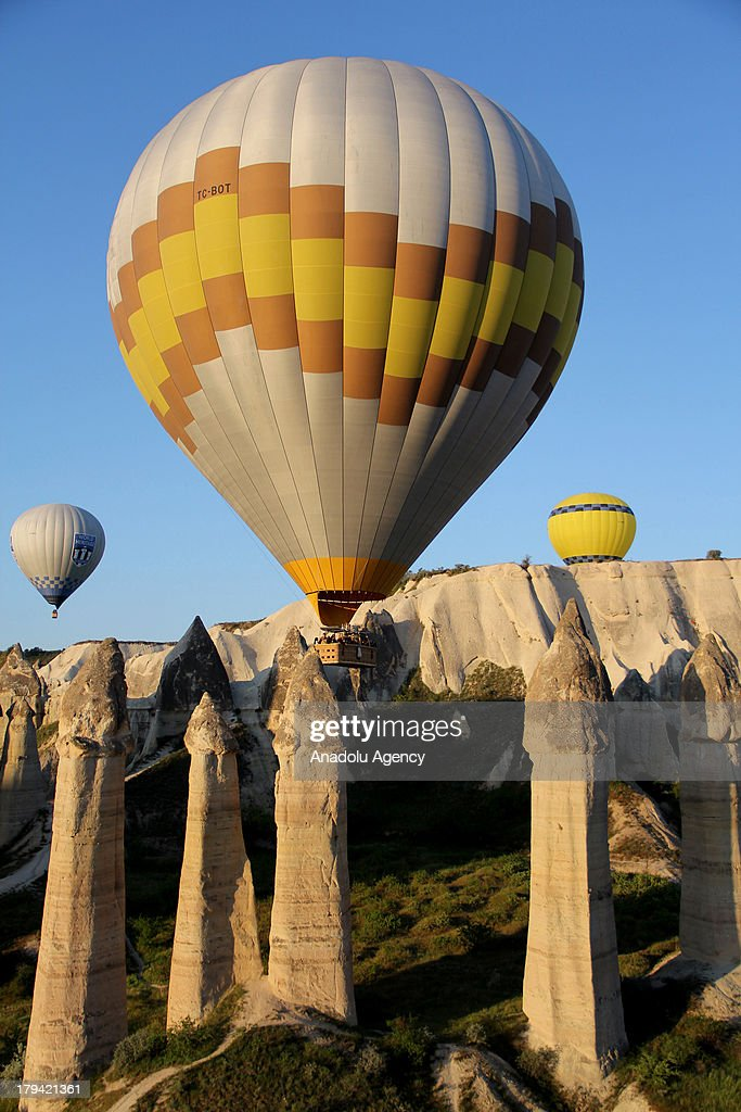 A hot air balloon rises above the the earth pillars on August 21, 2013 in Cappadocia, Turkey. Cappadocia, famous for its chimney rocks, hot air balloon trips, underground cities and boutique hotels carved into rocks, has received approximately 1.5 million national and international tourists in half a year, according to the statements released by the local governmental bodies. The historical region in Central Anatolia and one of the most popular tourism destinations in Turkey, offering attractions such as Goreme open-air museum, Kaymakli and Derinkuyu underground cities.