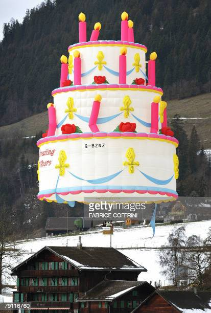 A hot air balloon shaped as a birthday cake flies above the Swiss Alps resort of Chateau d'Oex 19 January 200 at the opening day of the 30th...