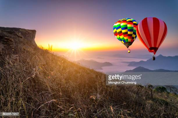 Hot air balloon with tourist is traveling into the peak of mountain and cloudscape at Phu chi fa in Chiangrai Provice, Thailand.
