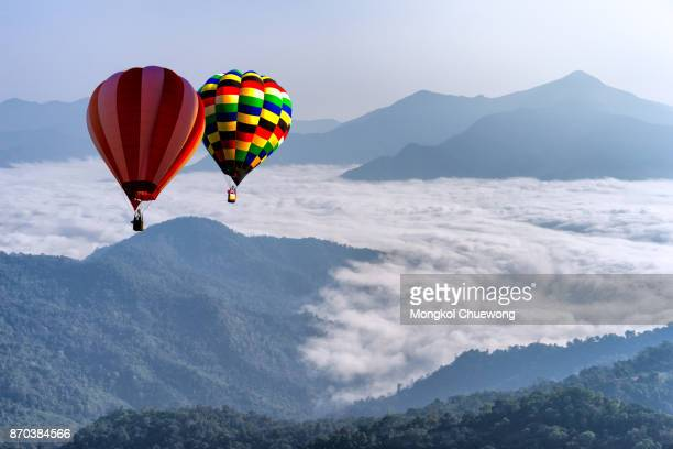Hot air balloon with tourist is traveling into the peak of mountain and cloudscape at Doi Pha Tang in Chiangrai Provice, Thailand.