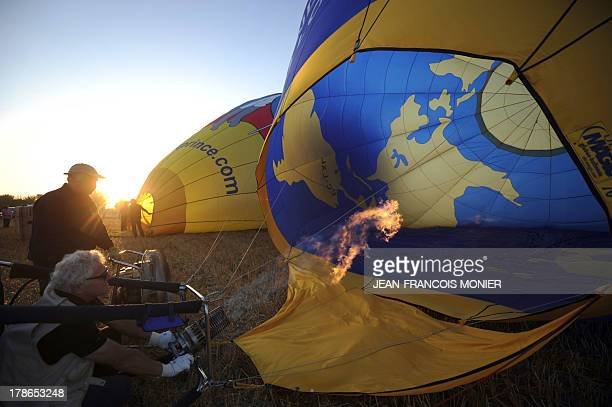 Hot air balloonists inflate their balloons before flying during the 39th French AirBalloon Championship on August 30 in BrissacQuincé Western France...