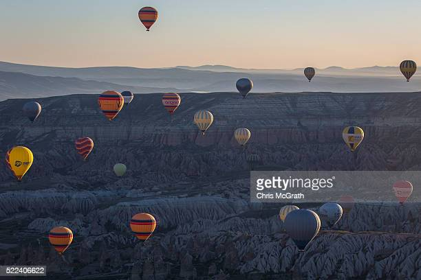 Hot air balloons are seen over rock formations near the town of Goreme on April 17 2016 in Nevsehir Turkey Cappadocia a historical region in Central...