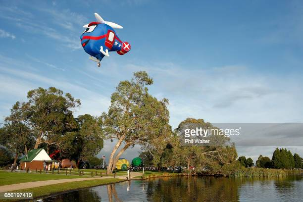 Hot air balloons begin to take to the air over the Hamilton Lake during the Mass Ascension on the opening day of Balloons Over Waikato on March 22...