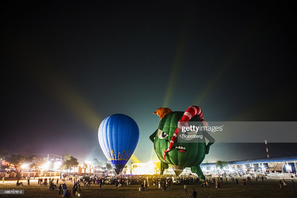 Hot air balloons fly as lights are beamed into the sky during an event titled 'Balloon Night Glow' at the fairgrounds of the Pushkar Camel Fair at...
