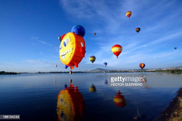 Hot air balloons fly over a lake during the International Balloon Festival at the Metropolitan Park in Leon Guanajuato state Mexico on November 15...