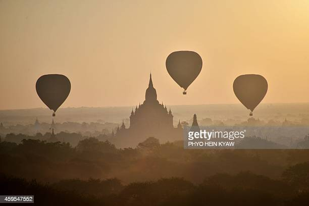Hot air balloons fly over ancient temples in Bagan northern Myanmar at sunrise on November 25 2014 AFP PHOTO/PHYO HEIN KYAW