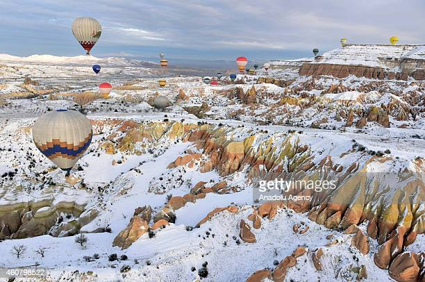 Hot air balloons fly over Cappadocia a historical region in Central Anatolia largely in Nevsehir Province known for the fairy chimneys during the...