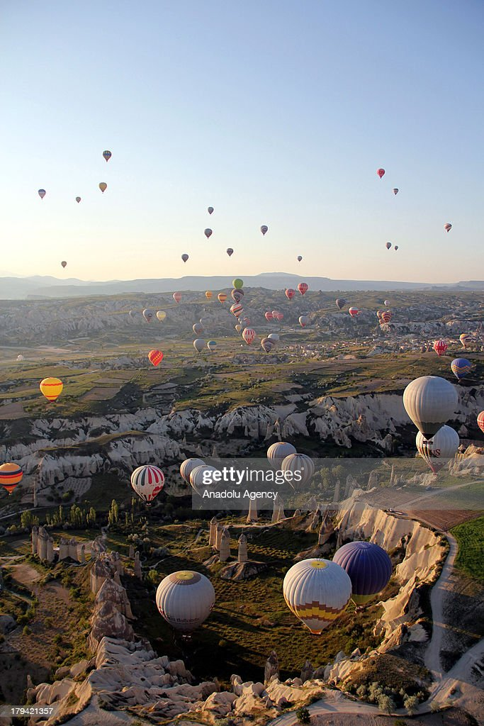 Hot air balloons fly over the earth pillars on August 21, 2013 in Cappadocia, Turkey. Cappadocia, famous for its chimney rocks, hot air balloon trips, underground cities and boutique hotels carved into rocks, has received approximately 1.5 million national and international tourists in half a year, according to the statements released by the local governmental bodies. The historical region in Central Anatolia and one of the most popular tourism destinations in Turkey, offering attractions such as Goreme open-air museum, Kaymakli and Derinkuyu underground cities.