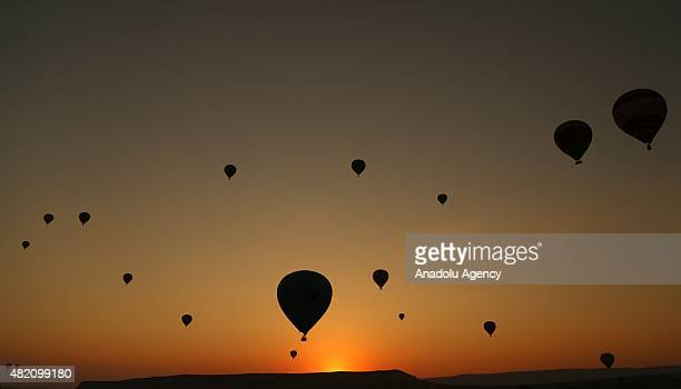 Hot air balloons fly over the famous volcanic rock formations during sunrise in Cappadocia a historical region in central Anatolia on July 27 2015 in...