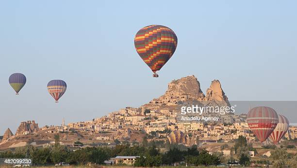 Hot air balloons fly over the famous volcanic rock formations in Cappadocia a historical region in central Anatolia on July 27 2015 in Nevsehir...