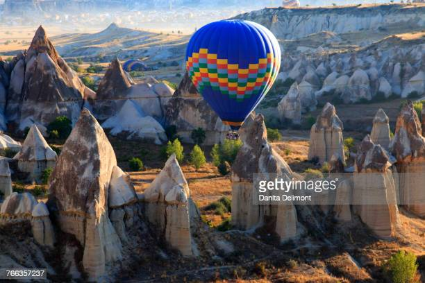 Hot air balloons flying above rock formations in Red Valley, Goreme National Park, Goreme, Cappadocia, Anatolia, Turkey