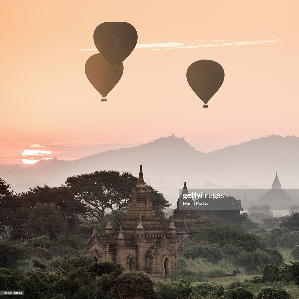 hot air balloons flying over temples at sunrise