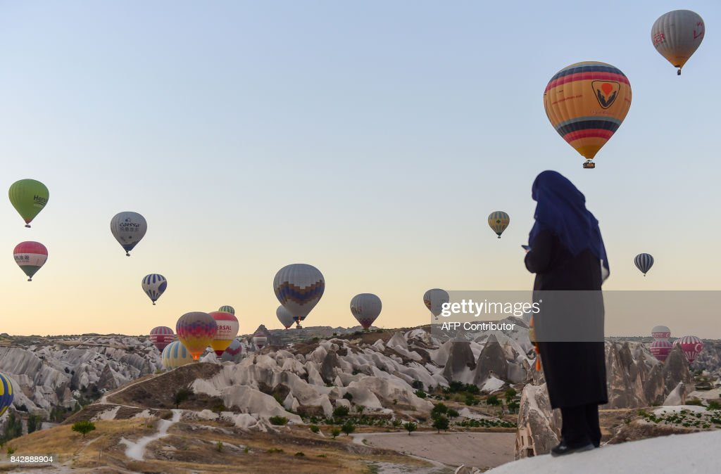 TOPSHOT - Hot air balloons glide during a flight over Nevsehir in Turkey's historical Cappadocia region, Central Anatolia, eastern Turkey, on September 5, 2017. The rides by hot air balloon start in the morning as the balloons cannot fly at temperatures over 28 degrees Celsius and during extreme windy conditions. Cappadocia is one of the most famous tourist sites in Turkey and has been listed as a World Heritage Site in 1985. /