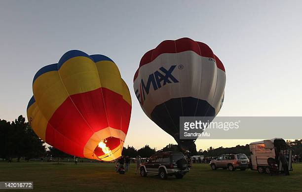 Hot air balloons inflate at Innes Common Park during a dawn lift on March 29 2012 in Hamilton New Zealand Each Autumn over 30 hot air balloons grace...
