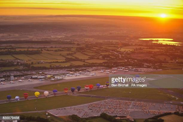 Hot air balloons line up on the main runway at Bristol International Airport at sunrise as they prepare to fly from the airport for the first time