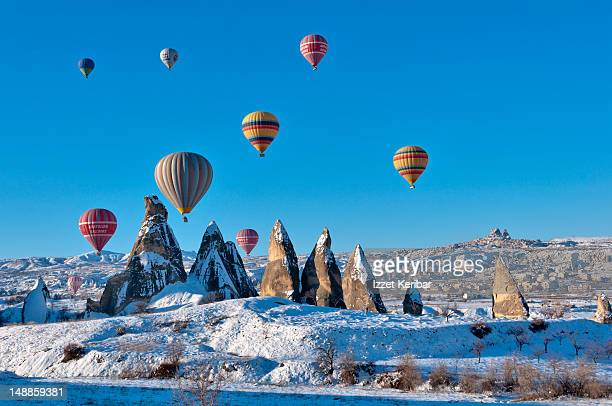 Hot air balloons over snow covered rock formations.