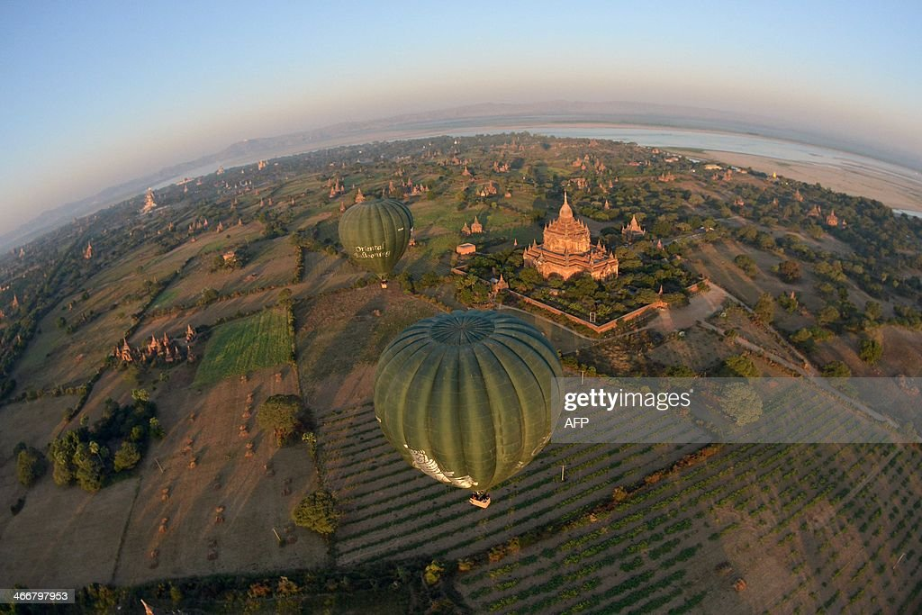 Hot air balloons provide a view of the temples as they hovers over Bagan in Myanmar on February 4, 2014. Between the 11th and 13th centuries, Bagan in Mandalay province in Myanmar was the kingdom's capital, one of the most important centres for learning in Asia, if not the world. The kings and rulers built thousands of temples, more than 3,000 of which are still standing today. The city is one of the Myanmar's most treasured religious sites and attracts hundreds of visitors a day. But over the past 20 years, many of the temples have been renovated and now bear little resemblance to their original structures. AFP PHOTO / YE AUNG THU