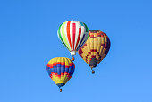 Hot air balloons soar in clear blue sky