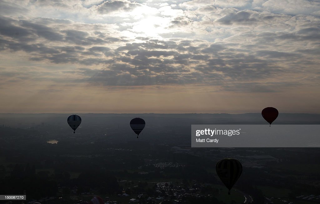 Hot air balloons take to the skies from Ashton Court at the Bristol International Balloon Fiesta on August 10 2012 in Bristol England The early...