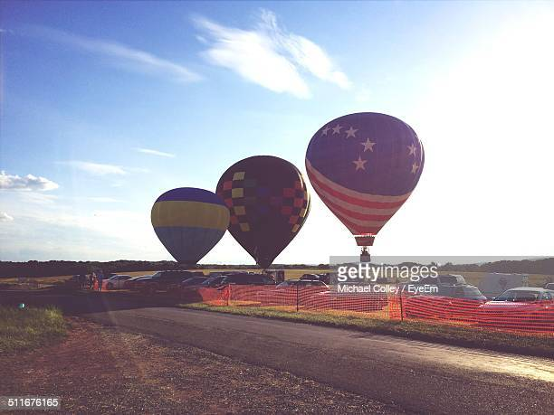 Hot air balloons taking off from landscape against blue sky