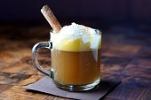 Hot Buttered Rum cocktail with whipped egg whites and a cinnamon stick.