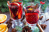 hot christmas mulled wine with snow, cinnamon sticks, anise and orange on wooden table background with fir branches and pine cones