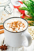 Hot cocoa (coffee or chocolate) with marshmallows and cinnamon in a white Cup. Candy, candles and fir branches on the table. Christmas. New year. Rustic style. Selective focus