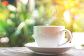 hot coffee cup on wooden table over nature green morning background