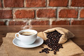 Hot coffee in white cup and roasted coffee beans, coffee cup on brick wall background