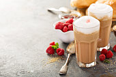 Hot coffee latte with thick foam and raspberry syrup
