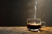 Hot coffee on a wooden table in the dark