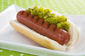 A plump grilled beef hot dog on a bun topped with sweet pickle relish.