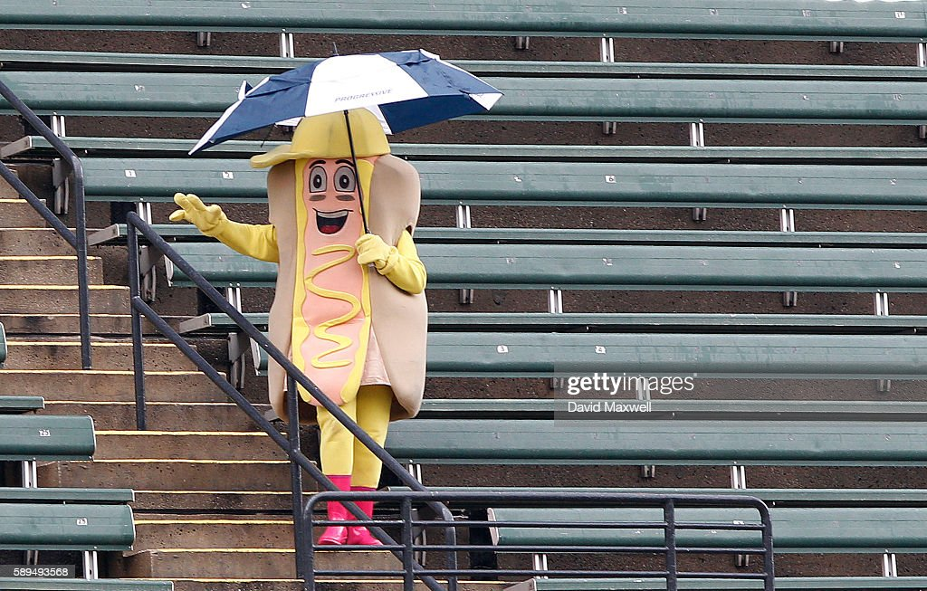 A hot dog mustard mascot dances in the bleachers during a rain delay before the game between the Cleveland Indians and the Los Angeles Angels of...
