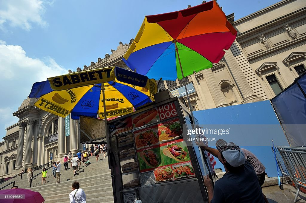 A hot dog vendor puts up another unbrella in front of the Metropolitan Museum of Art on July 19, 2013 in New York as a heatwave continues in the northeast. AFP PHOTO/Stan HONDA