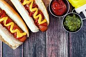 Hot dogs with mustard and ketchup, close up overhead scene on a rustic wood background