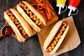 Traditional hot dogs with mustard, ketchup and fries. Top view scene on a rustic wood background.