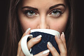 Closeup photo from a beautiful young woman drinking from mug