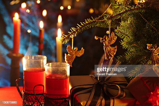 Hot drink, tea, grog, mulled wein with burning candels and gifts beneath a branch of a Christmas tree