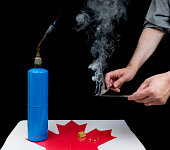 "Two hands holding table knives for doing ""hot knives"" of hashish. Knives are together with smoke rising. Table is a Canadian maple leaf with a block of blonde hash and several small spots. Black backg"