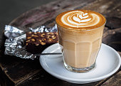 A cup of hot latte art or cappuccino coffee on old wooden table with brownie cake on foil