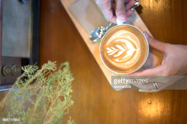 hot latte coffee on wooden space with tablet and smart-phone