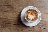 hot latte served in orange cup with latte art in fern shape